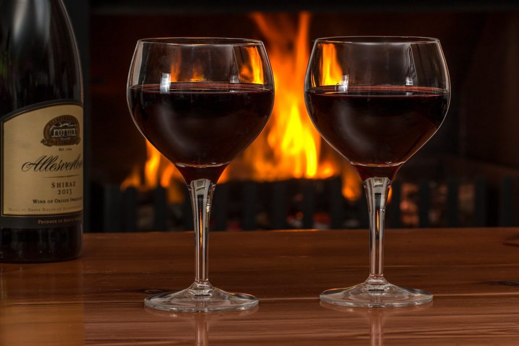 Image of two glasses of wine with a bottle behind them